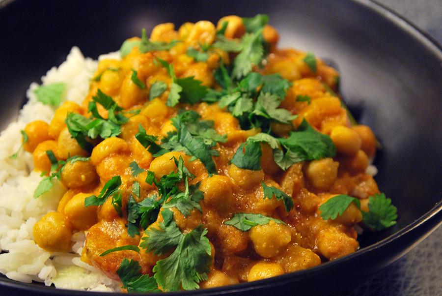 Svart tallrik fylld med en currygryta med kikärtor och jordnötter